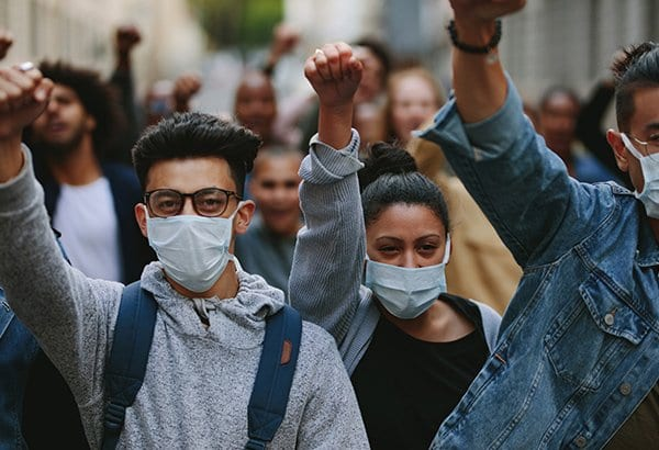 Young adults wearing surgical masks at a protest
